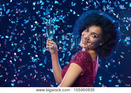 Party, drinks, holidays and celebration concept. Happy mixed race woman in sequined dress with glass of sparkling wine over colorful background with confetti looking to the side at blank copy space
