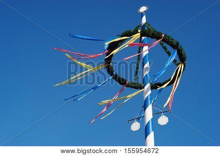 traditional multi colored bavarian maypole against blue sky