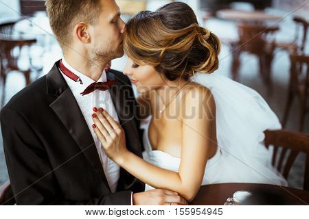 Wedding photo shooting. Bride and bridegroom sitting in cafe. Bridegroom kissing bride's forehead. Outdoor, waist up, profile, closeup