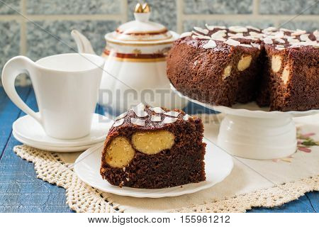 Baking in multicooker. Delicious homemade chocolate cake with curd-coconut balls on a blue wooden table. Decorated with coconut crunch. Served with tea
