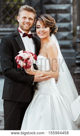 Wedding photo shooting. Bride and bridegroom smiling and embracing. Holding bouquet. Outdoor