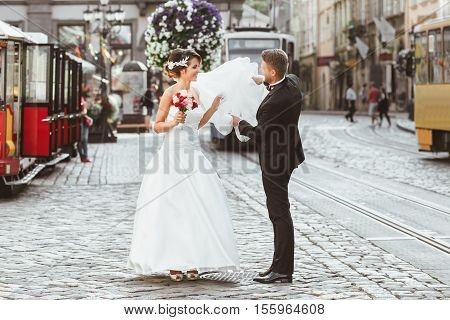 Wedding photo shooting. Bride and bridegroom walking in the city. Husband holding his wife's veil. Looking at each other, holding bouquet. Outdoor, full body. Tram, cobbled street