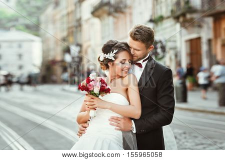 Wedding photo shooting. Bride and bridegroom walking in the city. Man embracing girl's waist from back. Outdoor, cobbled street