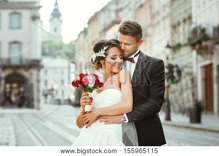 Wedding photo shooting. Bride and bridegroom walking in the city. Man embracing girl's waist from back. Bride looking aside and smiling. Outdoor, cobbled street