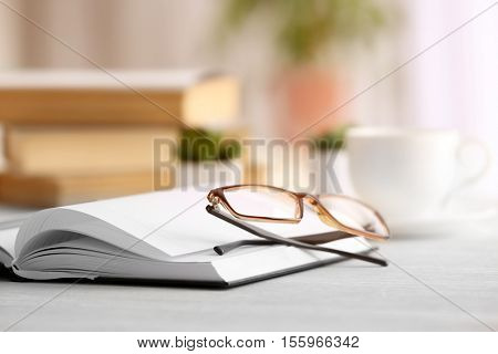 Glasses and notebook on wooden table. Healthy eyes concept