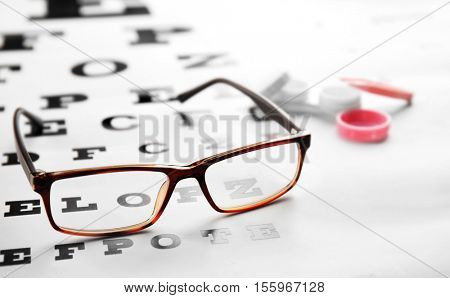 Glasses lying on eye test chart, close up view. Healthy eyes concept