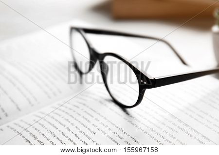 Glasses on open book, close up view. Healthy eyes concept