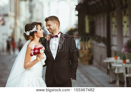 Wedding photo shooting. Bride and bridegroom at street Looking at each other, holding bouquet. Outdoor