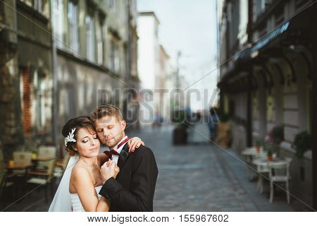 Wedding photo shooting. Bride and bridegroom at street. Embracing with closed eyes. Outdoor, waist up