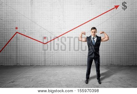 An athletic businessman full-height in a jacket without sleeves with his arms showing muscles on the background of the big graph with the arrow pointing up at a dollar sign. Business and management. Statisics and data. Getting profit. Way to success.