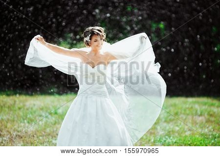 Wedding photo shooting. Bride under rain, holding her fluttering veil. Looking aside. Wearing white dress and long veil. Outdoor