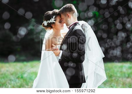 Wedding photo shooting. Bride and groom under rain, holding hands of each other. Very close to each other. Closed eyes. Outdoor