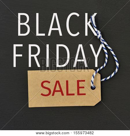 text black friday written in white and the word sale written in red in a brown paper label against a dark gray background