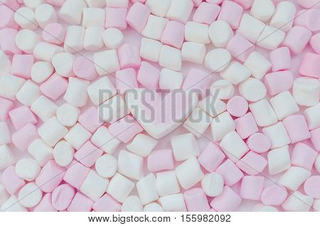 Pink and white mini marshmallows background with heart close-up texture. A pile of different mini puffy marshmallows. Marshmallow concept. Wallpaper for desktop. Top view.