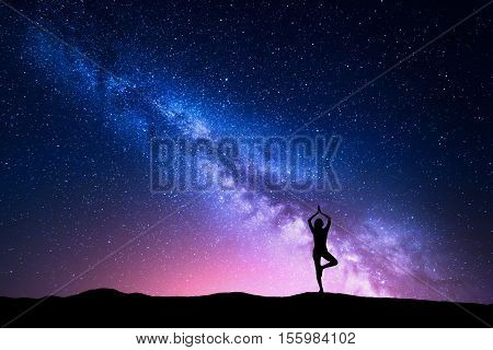 Milky Way with silhouette of a standing woman practicing yoga on the mountain. Beautiful landscape with meditating girl against night starry sky with milky way. Amazing galaxy. Universe. Travel
