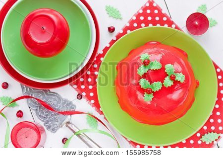 New Year and Christmas cake with red mirror glaze and holly decoration. Traditional Christmas pudding recipe