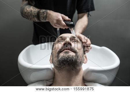 Handsome man with a beard in the barbershop. His head lies in the white sink and a barber with tattoo washes it with a black faucet. Guy looks up. Closeup. Horizontal.