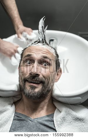 Funny man with a beard lies on the white sink in the barbershop. He has the lathered head with the punk hairstyle. Guy looks to the side with a grimace. Closeup. Vertical.