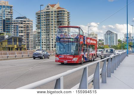 Brisbane, Australia - September 25, 2016: View of sightseeing open top double decker bus and cars on the bridge with modern buildings in Brisbane.