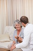 stock photo of health-care  - Doctor talking with his patient at home - JPG