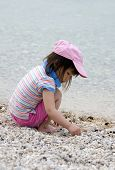 picture of pick up  - A young girl picks up rocks on the beach - JPG