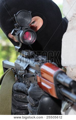 Sniper In Black Mask Targeting On Scope