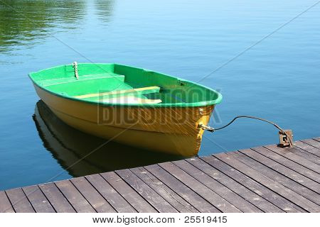 A Small Boat Parking At A Wood Dock