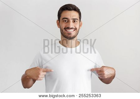 poster of Smiling Nice Man Pointing At Blank White T-shirt With Both Index Fingers, Copy Space For Your Advert