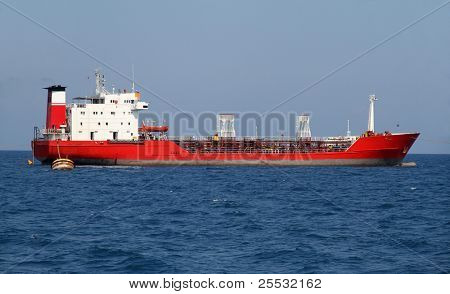 Red tanker designed for transporting crude oil is at anchor near the port