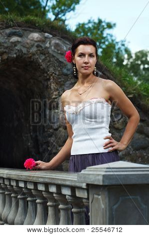 Brunette Woman With Flower On Antique Stone Wall Background.
