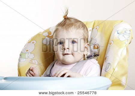 Baby Girl With Hairpin Sitting On High Chair.