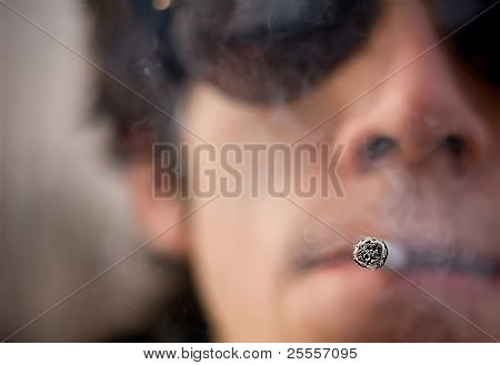 Caucasian man holding 1 cigar in his mouth. defocused background