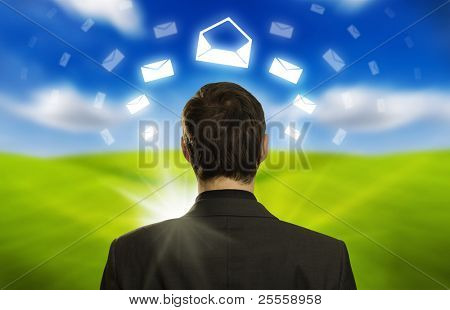 Young businessman with e-mail icons floating around his head