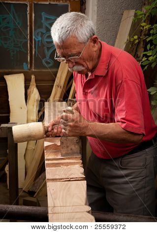 Old woodcarver working with mallet and chisel 3