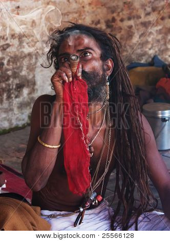 KATHMANDU, NEPAL -  OCTOBER 27 : Shaiva sadhu (holy man) smokes a pipe in the colonnade of the temple Pashupatinath on October 27, 2010 in Kathmandu valley, Nepal.