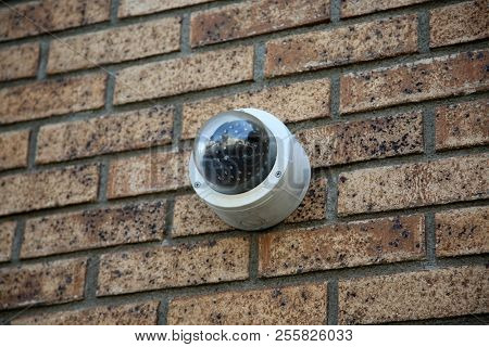 poster of Security Camera. Security Camera attached to a wall of a building. Video Camera.