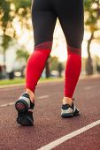 Close Up Of Womens Shoes Walking Outdoors In Running Shoes From Behind. Black And Pink Sportswear A poster