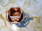 Drip Fresh Coffee Sachets On The Transparent Glass Coffee Cup With Dripped Coffee Inside. poster