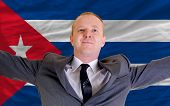 Happy Businessman Because Of Profitable Investment In Cuba Standing Near Flag
