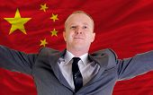 Happy Businessman Because Of Profitable Investment In China Standing Near Flag