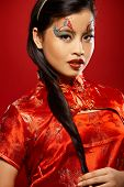 stock photo of asian woman  - Beautiful Asian girl as a plastic doll on red background - JPG