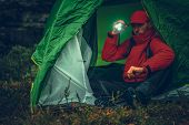 Caucasian Camper With Flashlight Inside His Tent During Rainy Evening While On Hike. poster