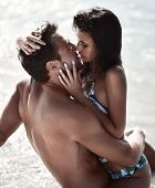 Happy Cheerful Couple Kissing Hugging In The Sea Together With Splashes Of Water On A Tropical Beach poster