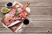 Salami, sliced ham, sausage, prosciutto, bacon, toasts, olives. Meat antipasto platter and red wine  poster