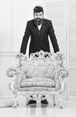 Macho Attractive And Elegant On Smiling, Thoughtful Face Lean On Old Fashioned Armchair. Fashion And poster