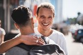 Satisfied Friends Embracing During Meeting At Street poster