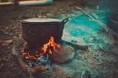 Camp And Cooking In Field Conditions, Boiling Pot At The Campfire On Picnic In Morning.  Cooking Din poster