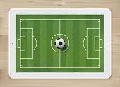 Soccer Football Ball In Soccer Field Area On Tablet Display With Wood Texture Background. For Create poster