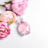 Pink Perfume Bottle With Flowers On Light Background. Perfumery, Cosmetics, Fragrance Collection. Fr poster