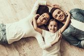 Happy Family Lying Of Floor Together At Home. Beautiful Woman Handsome Man And Adorable Little Girl  poster